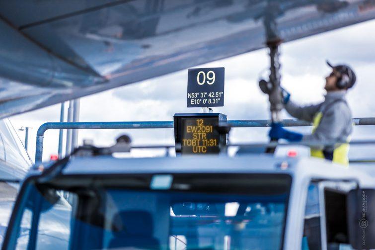 Airplane being refueled, Airport gate signage, Hamburg Airport | © Eric Shambroom Photography